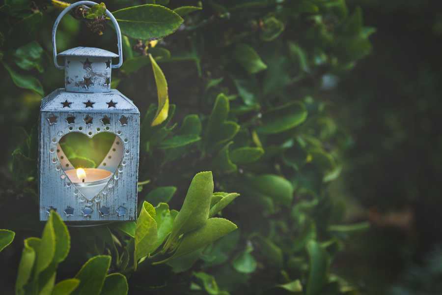 Vintage Metal Heart Shape Candle Holder Lit Burning Flame Hanging on Tree Branch in Garden. Flickering Sparkling Light. Romantic Magical Atmosphere. Valentine Mother's Day Wedding Engagement