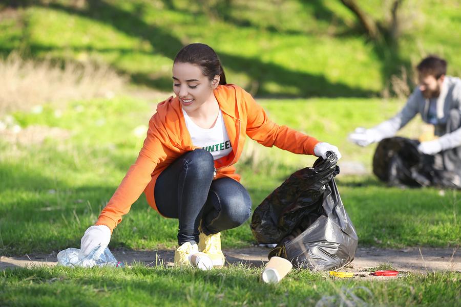 Volunteer picking up litter in park after bonfire night