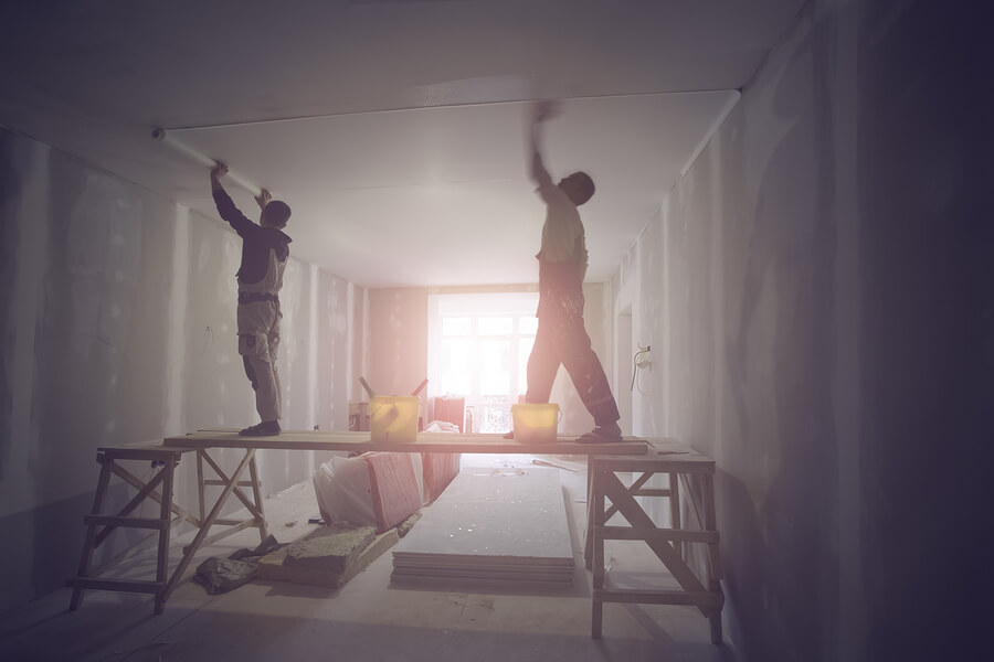 Workers painting a living room that is being refurbished.
