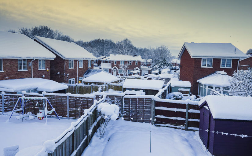 A picture of snow covered gardens and houses.