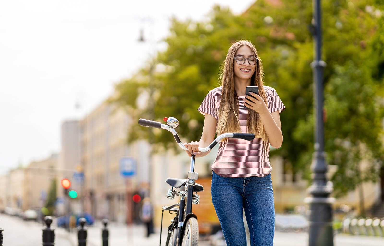A woman on her bike while holding her phone.